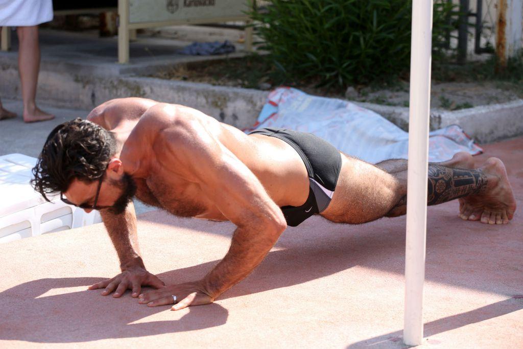 Mišićavi muškarac radi sklekove na splitskim Bačvicama
