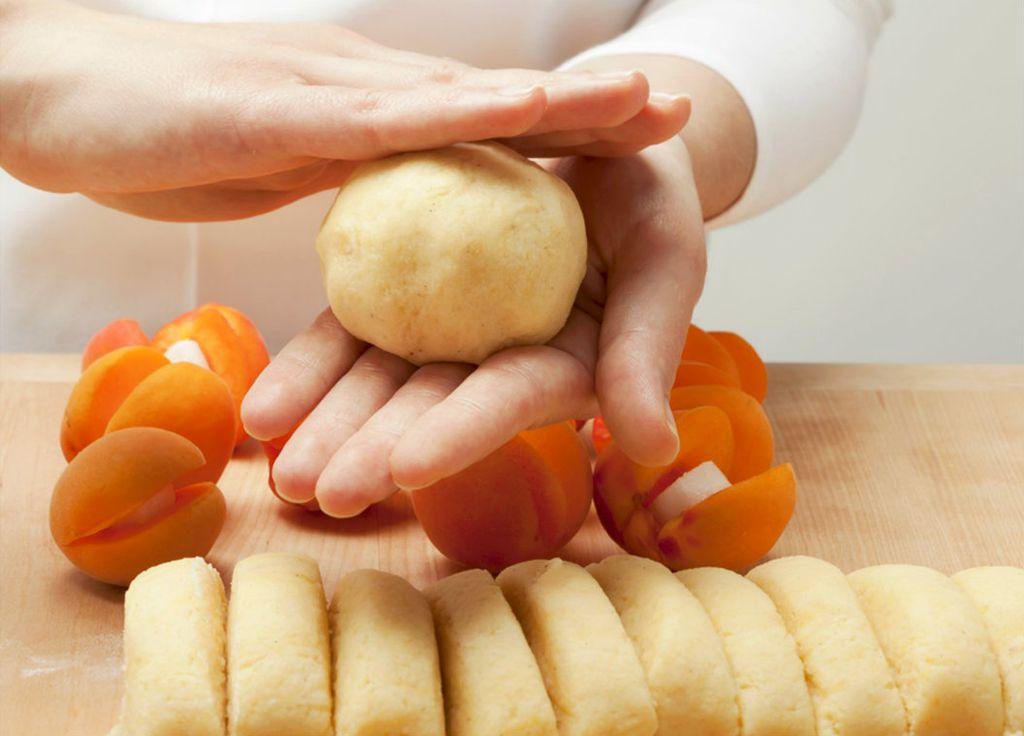 Prstima tijesto povlačite preko marelice i na kraju dlanovima zagladite dobivenu kuglu