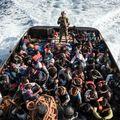 Pripadnik libijske obalne straže s presretnutim migrantima (Foto: AFP)