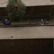 Bacanje jelke s balkona