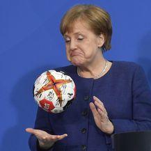 Angela Merkel s rukometnom loptom potpisane od strane njemačke rukometne reprezentacije