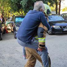 Vatrogasac nosi teško pokretnog muškarca na leđima - 2