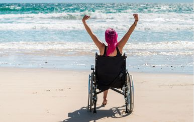 Žena u invalidskim kolicima na plaži