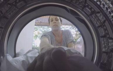 Žena ubacuje odjeću u perilicu rublja