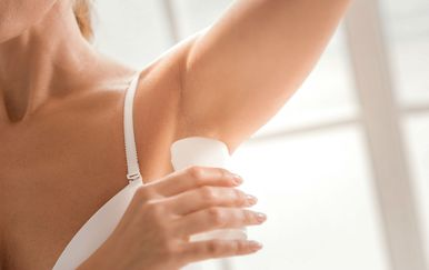 Žena nanosi dezodorans