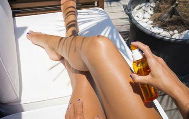 Žena nanosi sprej za sunčanje