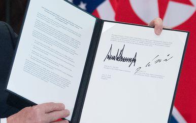 Donald Trump pokazuje dokument koji je potpisao s Kim Jong Unom u Singapuru (Foto: AFP)