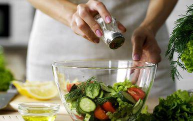 Žena soli salatu