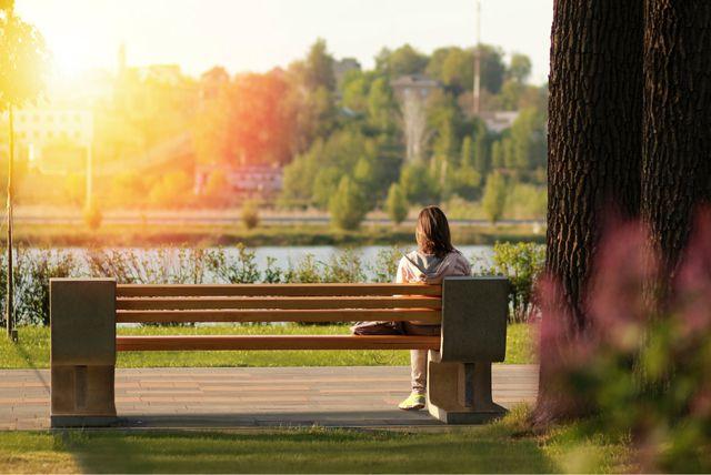 Žena sjedi na klupi u parku