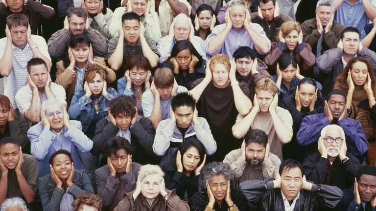 Mnoštvo ljudi s rukama preko ušiju