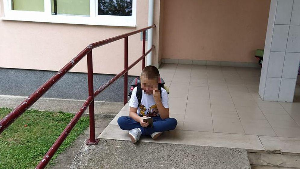 Dječak ispred škole čeka pomoćnika u nastavi (Foto: Facebook)